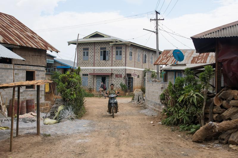 Man riding motorcylce in local dirt road with colorful houses near inle lake in myanmar stock photo