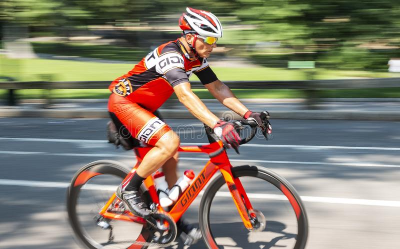 Man riding orange racing bike on road blurred background stock photography