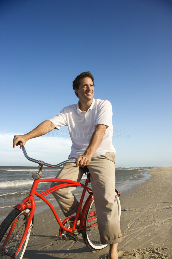 Man riding red bicycle on beach. royalty free stock images