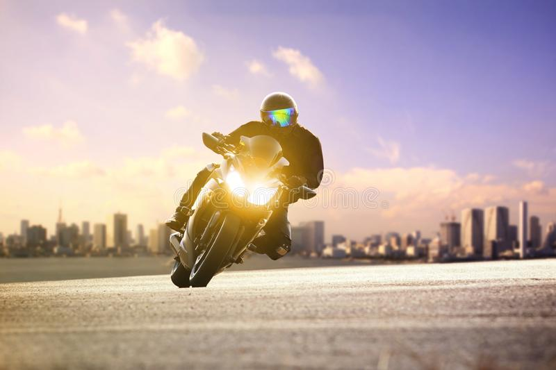 Man riding sport motorcycle lean on curve road against urban skyline background royalty free stock images