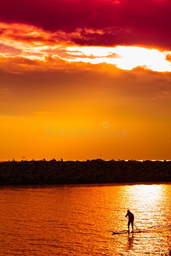 Man riding on a stand up paddle board SUP on a waterway under an orange sky. The photo is taken off of Dana Point in Southern California royalty free stock image