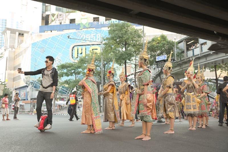 Man ridningenhjulingen som tar selfie med gruppen av thailändska traditionella dansare fotografering för bildbyråer