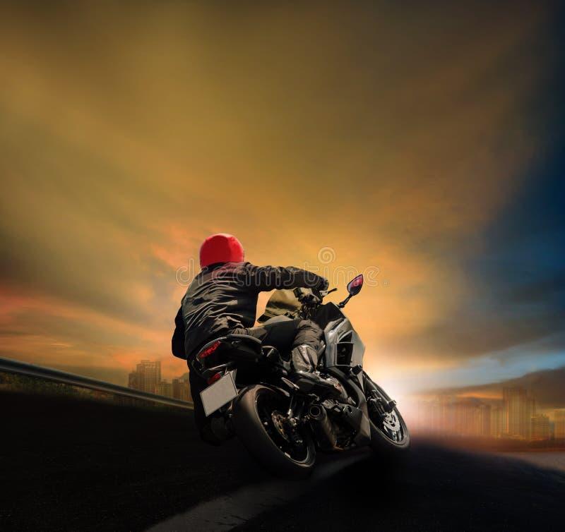 Man ridningmotorcykeln på asfalthuvudvägen mot solnedgånghimmel royaltyfri bild
