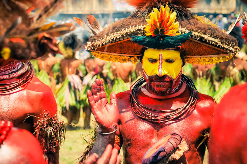 Man with risen hand. Wabag, Papua New Guinea - August 2015: Native half-naked man with red and yellow colour on his face and body wears large hat with feathers royalty free stock photo