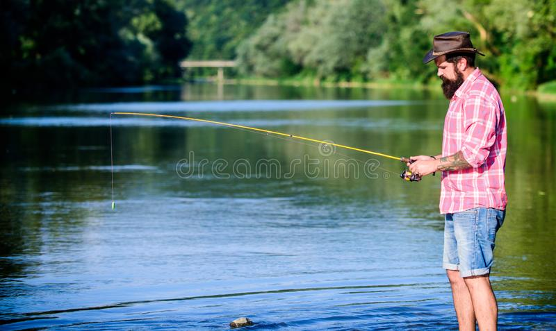 Man at riverside enjoy idyllic landscape while fishing. Fishing cause negative physiological effects for fish royalty free stock photos