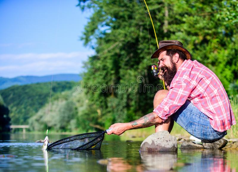 Man at riverside enjoy peaceful idyllic landscape while fishing. United with nature. Fisherman fishing technique use rod royalty free stock photo