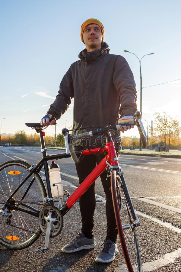 Man with road bike. Athletic young man stands with road bike on the road stock photos