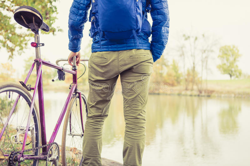 Man with road bike looking at river view in park. Male commuter and fixed gear bicycle relaxing in green park. Sport fitness motivation and inspiration in stock photos