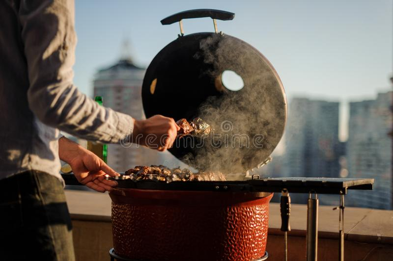 Man roasting a large meat pieces on the skewer in the grill on the blurred backround of city stock photos