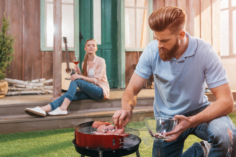 Man roasting meat on barbecue grill with woman with wine behind. Bearded men roasting meat on barbecue grill with women with wine behind stock images