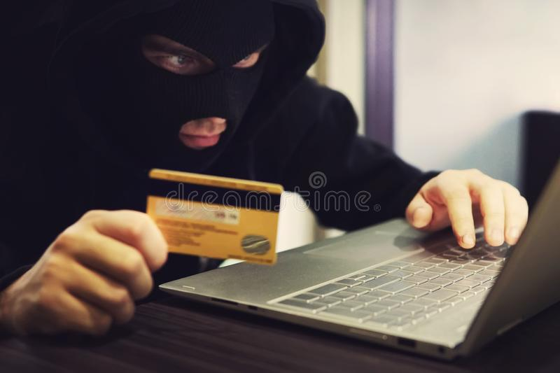 Man in robber mask and hood misappropriates personal bank data. Cyber fraudster attacks online banking system. Hacker. Makes financial fraud via internet stock photography