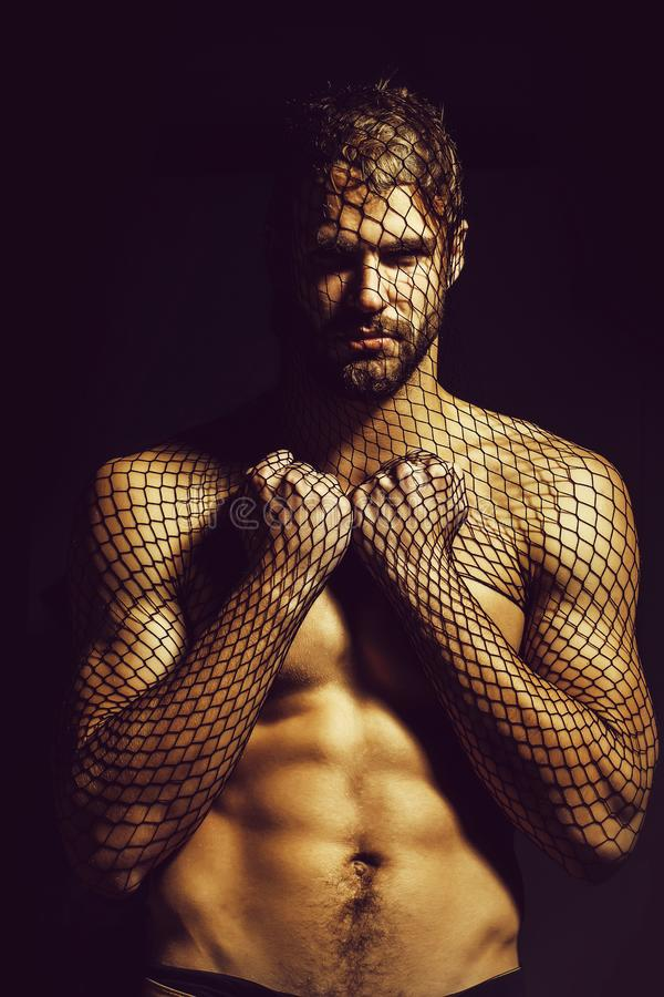 Man robber wears mask. Young handsome man bearded guy with beard or robber bandit gangster wears mask of black fishnet stocking on face on dark background with royalty free stock images