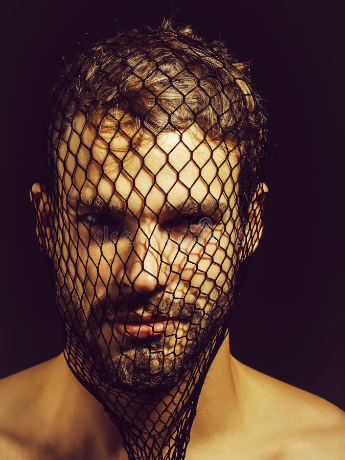 Man robber wears mask. Young man blond bearded male with beard or robber bandit gangster wears mask of black fishnet stocking on face on dark background stock image
