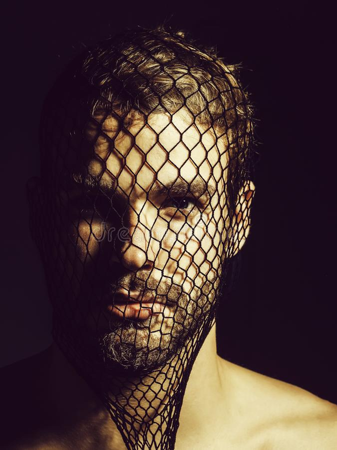 Man robber wears mask. Young man blond bearded male with beard or robber bandit gangster wears mask of black fishnet stocking on face on dark background royalty free stock photo