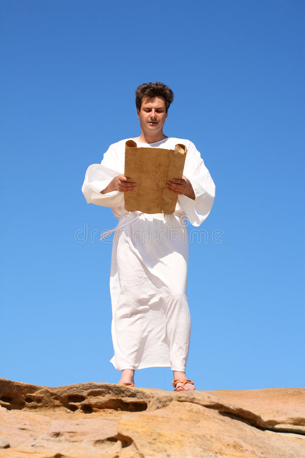 Man in robe reading. Ancient man in white robe reading from parchment scroll royalty free stock photos