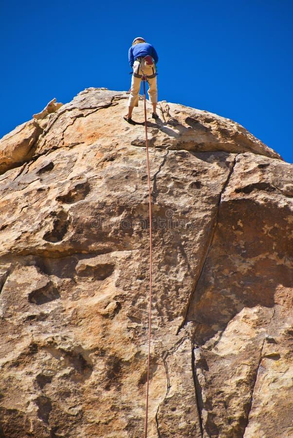 Man rock climbing, Joshua Tree National Park stock image
