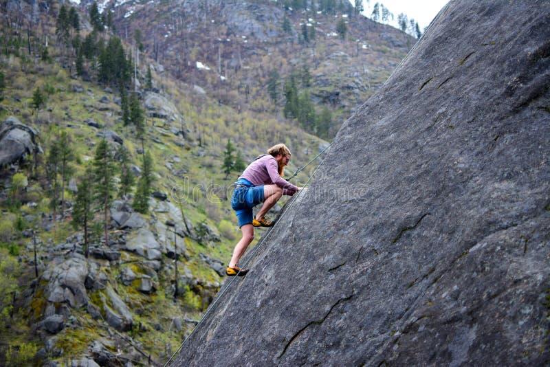 Man rock climbing stock image
