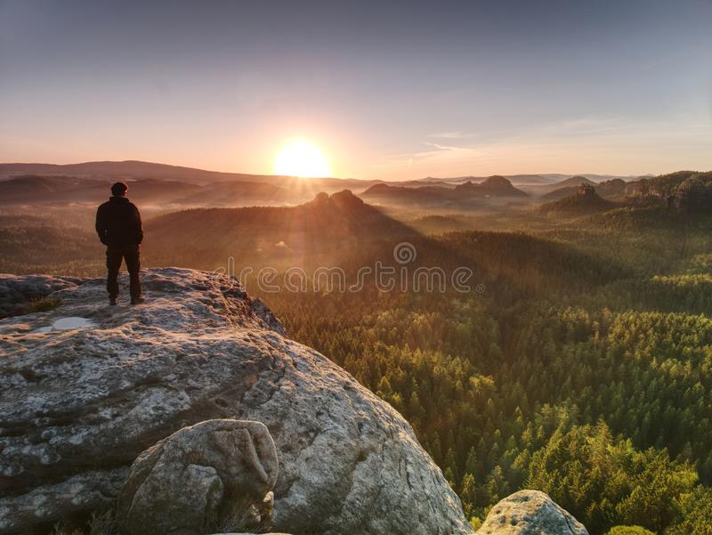 Man on rock with hands in trousers pocket  watch enjoy daybreak royalty free stock photos