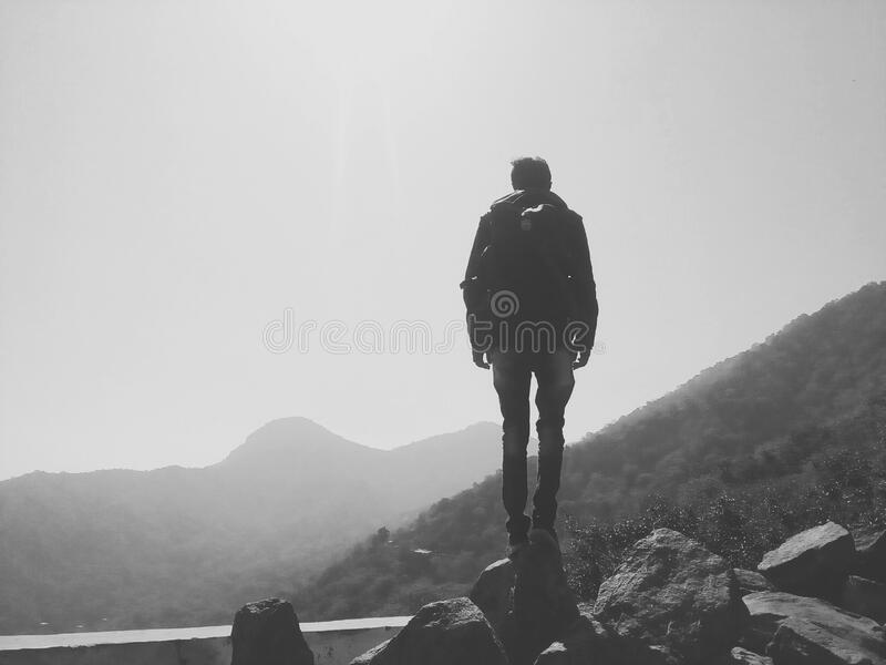 Back Of Man Standing On Boulder On Mountain Side With Fog In Black And White