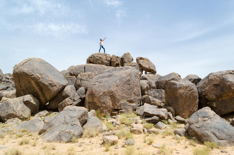 Man on rocks pointing his finger to the sky stock image
