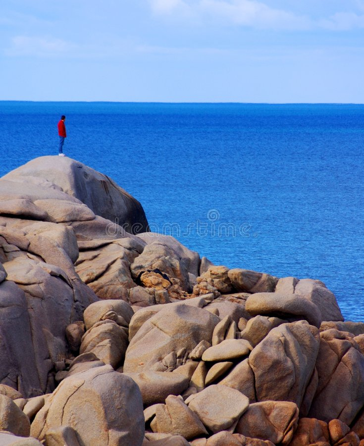 Man on rocky Cliff looking over the edge. Man on a rocky outcrop/cliff looking over the edge (Port Elliott, South Australia royalty free stock photography