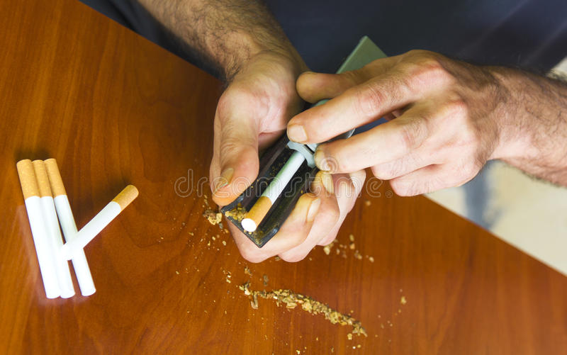 Man rolling cigarettes using fresh tobacco. Closeup royalty free stock photos