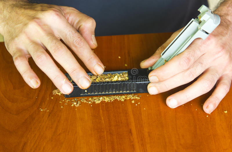 Man rolling cigarettes using fresh tobacco. Closeup stock photography