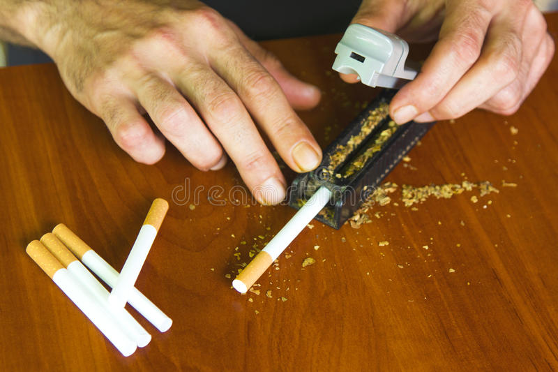Man rolling cigarettes using fresh tobacco. Closeup stock photos