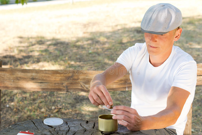 Man rolling himself a cigarette. From a small container of fresh tobacco blend while sitting on a wooden park bench royalty free stock photo