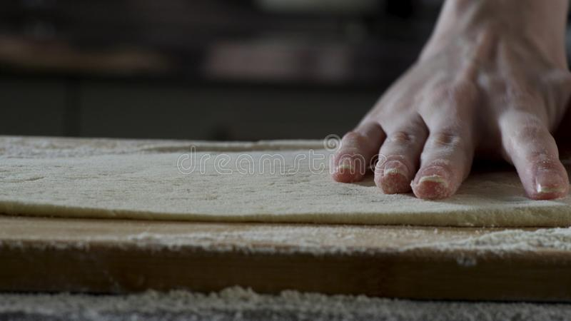 Man rolling out dough on kitchen table, close up. Scene. The cook rolls a piece of dough on the kitchen table with a stock photo