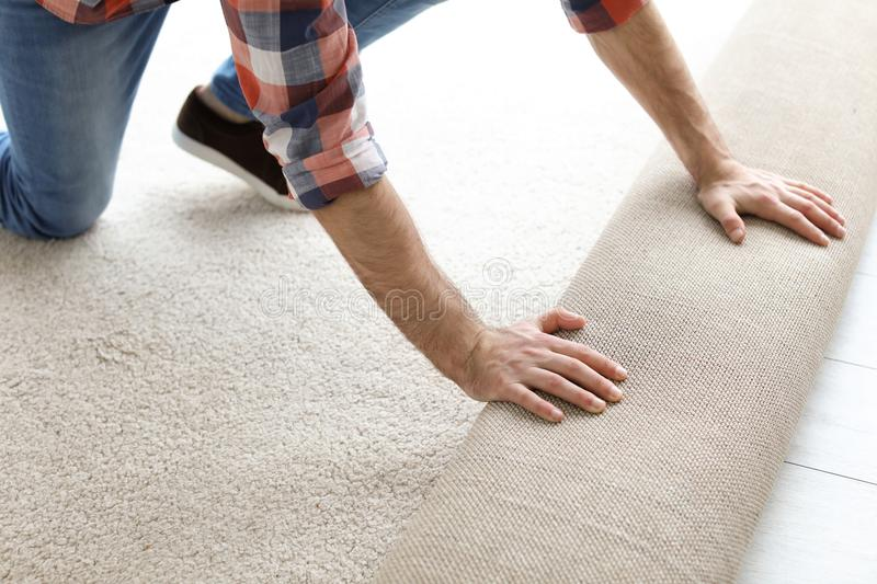 Man rolling out new carpet flooring stock images