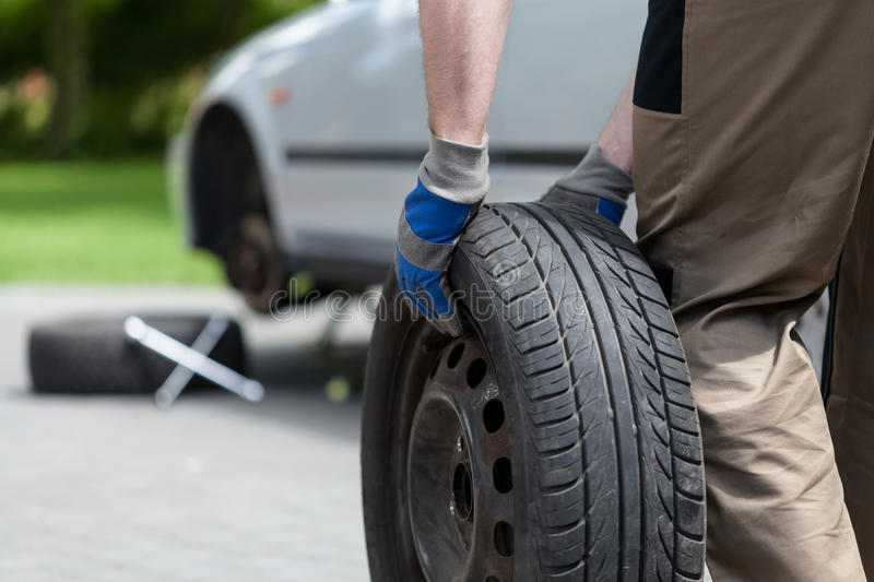Download Man Rolling A Spare Wheel Stock Photo - Image: 42532254