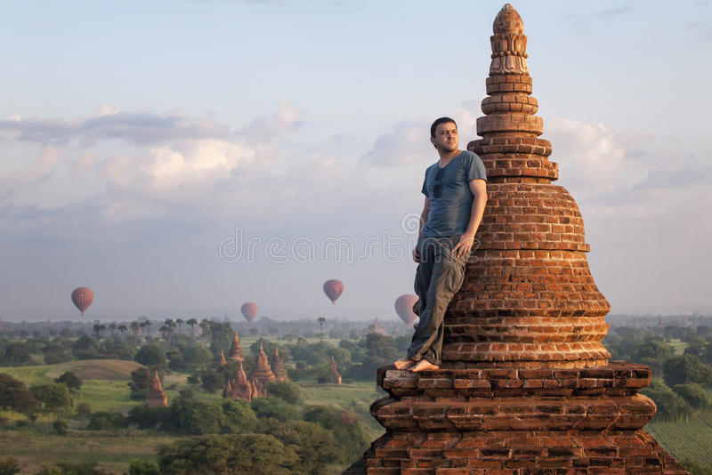 Man in a romantic pose standing on the roof against the backdrop of the city of Bagan and balloons. Myanmar royalty free stock image