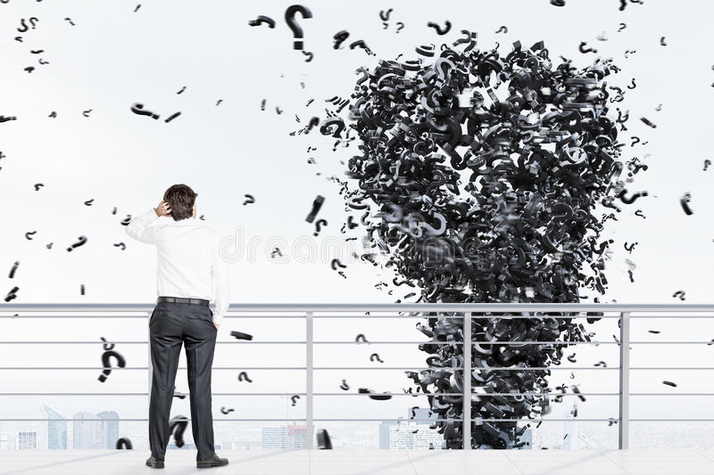 Man on a roof and a question mark tornado. Rear view of a young businessman wearing a white shirt standing on a balcony of a skyscraper looking at a question stock photo