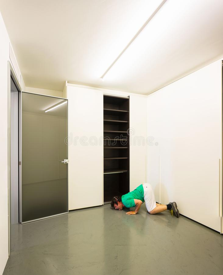 Man in a room. Man licks the floor near the closet royalty free stock images