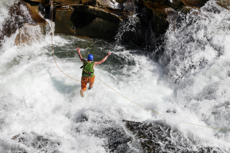 Man rope jumping in rapid waters of a river stock image