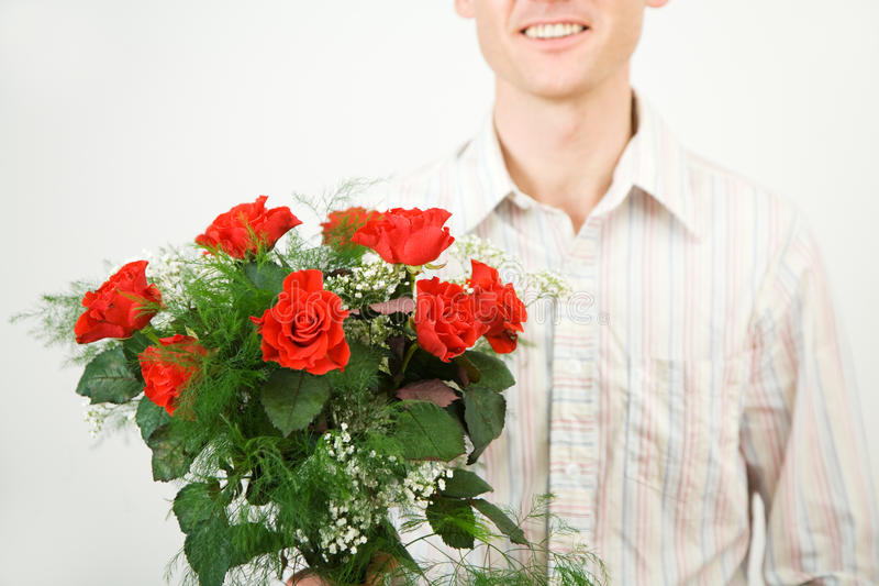 Man with roses. Man with a bouquet of red roses; shallow depth of field, focus on the roses stock photos