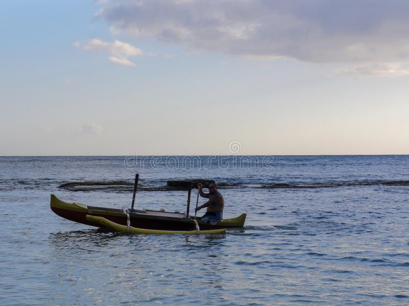 Man rowing boat in Hawaii. A man in a canoe off the coat of the island of Oahu in Hawaii royalty free stock photos