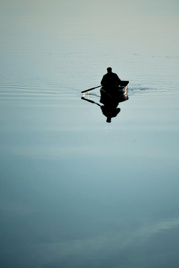 Man in a rowing boat oars in the water. One man in a small boat sailing boat on the lake river rowing oars. River with a smooth mirror surface of the water stock photos