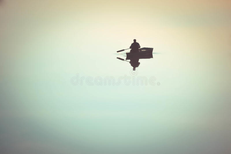 Man in a rowing boat oars in the water. One man in a small boat sailing boat on the lake river rowing oars. River with a smooth mirror surface of the water stock photography