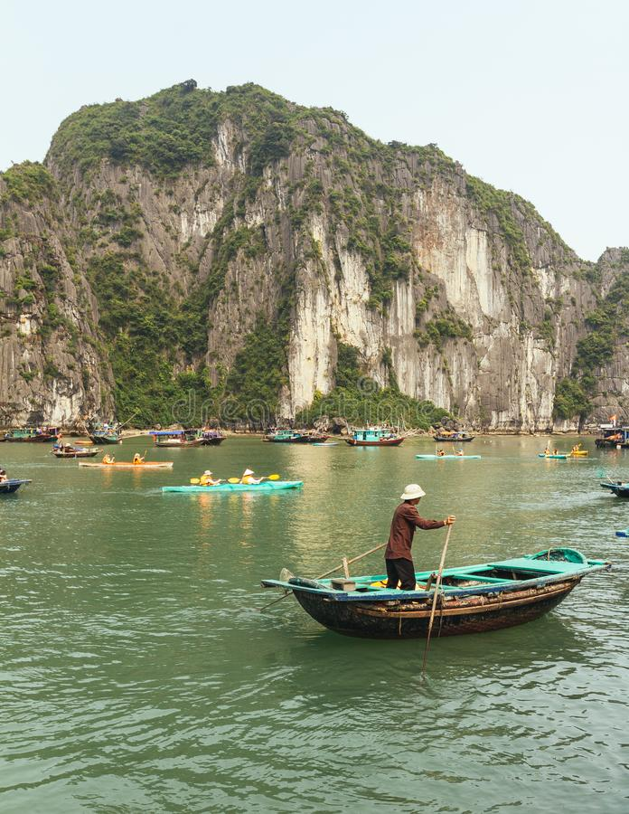 Man rowing boat over emerald water with limestone island in background in summer at Quang Ninh, Vietnam royalty free stock photos