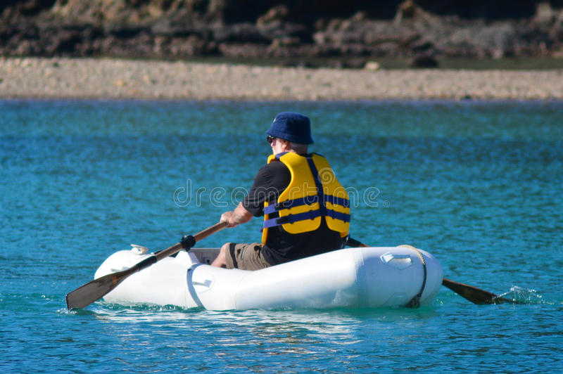 Man rows dinghy boat. Man rows a rubber inflatable dinghy boat stock photos