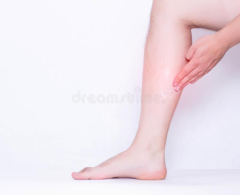 A man rubs a medical ointment in the damaged leg and calf muscle, a healing cream for stretching the ligaments and against. Inflammation, pain relief, copy stock images