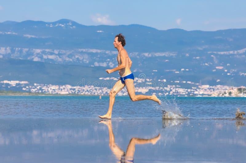 Man run across the beach stock photo