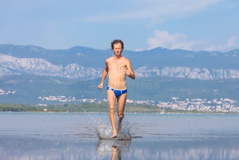 Man run across the beach royalty free stock photography