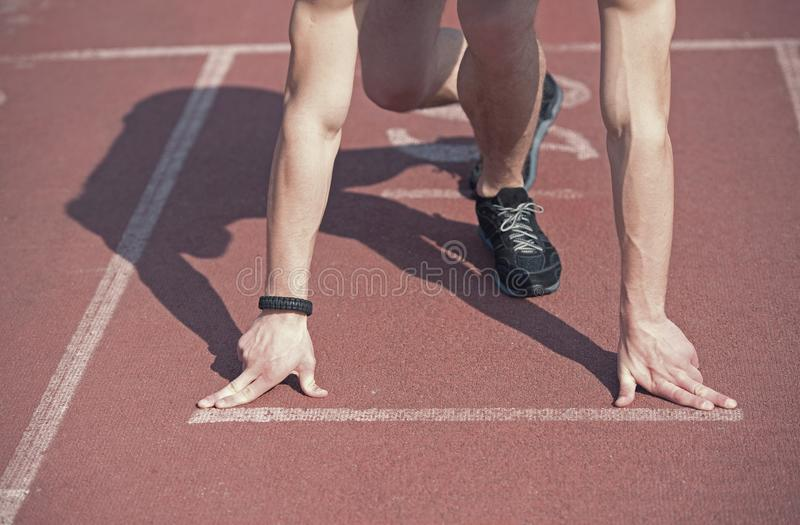 Man runner with muscular hands, legs start on running track. Man runner, athletic guy with muscular hands and legs start on running track or treadmill in black stock photos