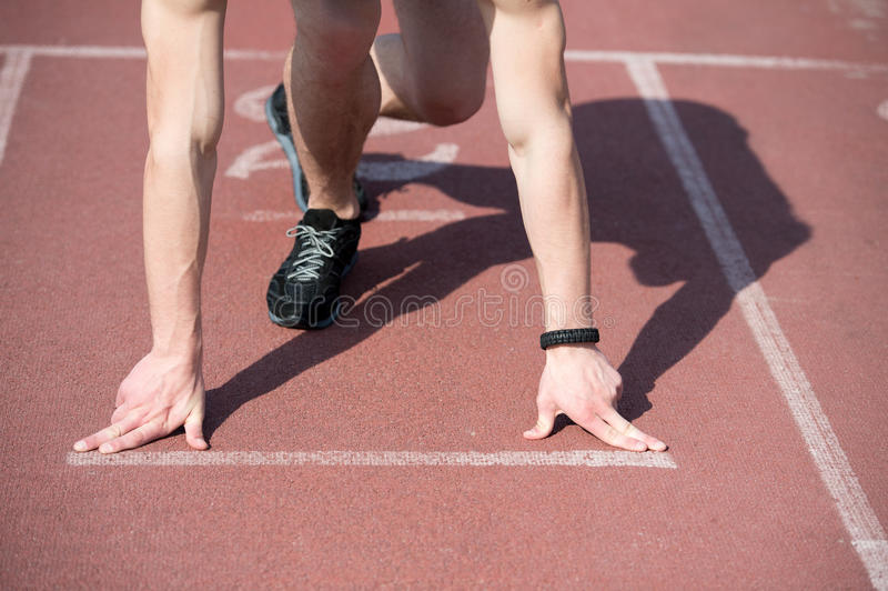 Man runner with muscular hands, legs start on running track. Man runner, athletic guy with muscular hands and legs start on running track or treadmill in black royalty free stock image