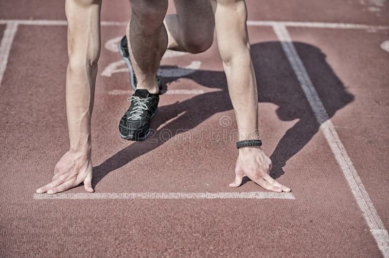 Man runner with muscular hands, legs start on running track. Runner at start, athletic guy with muscular hands and legs start on running track or treadmill in stock photography