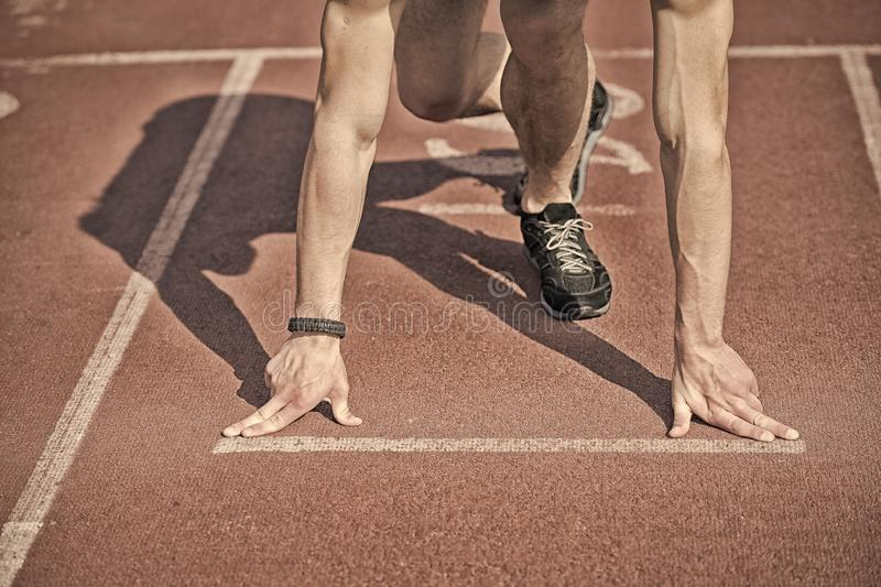 Man runner with muscular hands, legs start on running track. Runner at start, athletic guy with muscular hands and legs start on running track or treadmill in royalty free stock photography