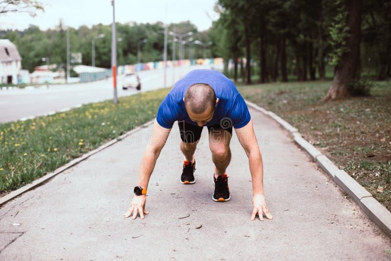 Man runner prepared for running in urban park stock images